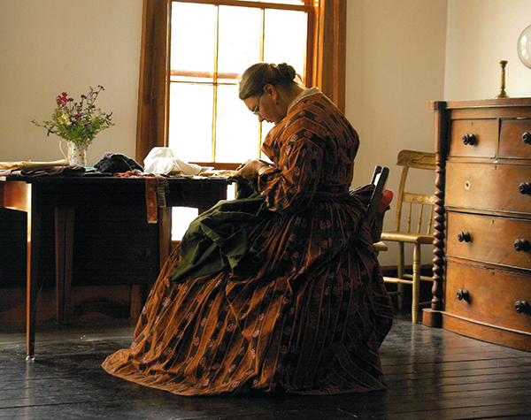 Women sewing inside historic historic setting at Old World Wisconsin
