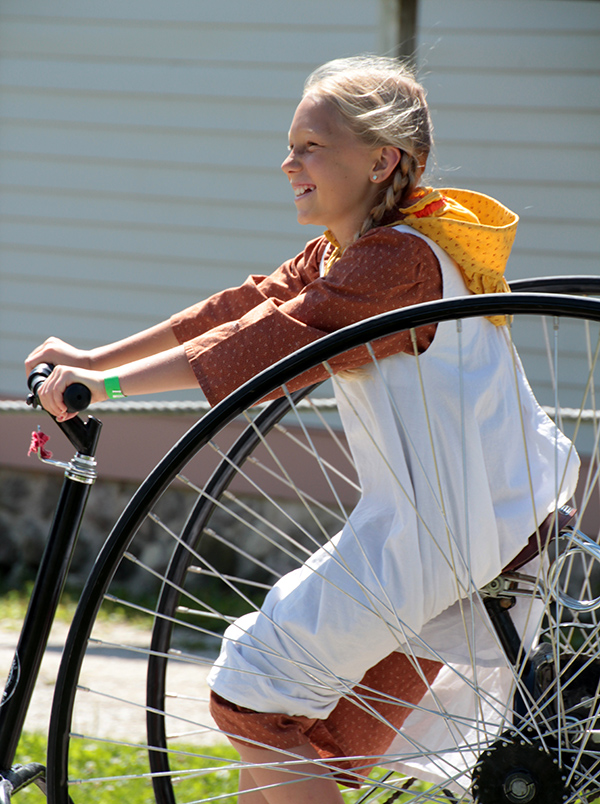 Girl riding vintage two-wheel bicycle at Old World Wisconsin.